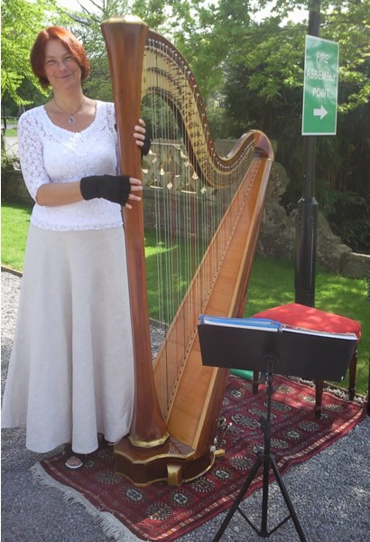 Marie France playing harp outdoors
